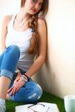 Giovane donna che si siede con il libro sull'erba Immagini Stock