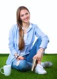 Giovane donna che si siede con il libro sull'erba Immagine Stock