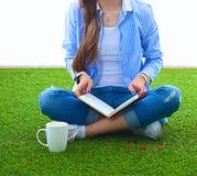 Giovane donna che si siede con il libro sull'erba Fotografia Stock Libera da Diritti