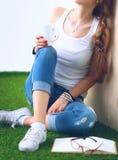 Giovane donna che si siede con il libro sull'erba Immagini Stock Libere da Diritti