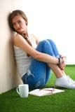 Giovane donna che si siede con il libro sull'erba Immagine Stock Libera da Diritti