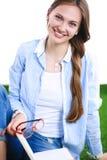 Giovane donna che si siede con il libro sull'erba Fotografie Stock Libere da Diritti