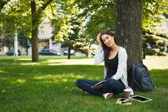 Giovane donna che si siede con il taccuino sull'erba Immagine Stock