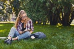 Giovane donna che si siede con il taccuino sull'erba Fotografie Stock Libere da Diritti
