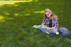 Giovane donna che si siede con il taccuino sull'erba Fotografia Stock Libera da Diritti