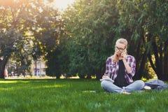 Giovane donna che si siede con il taccuino sull'erba Fotografie Stock