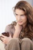 Giovane donna che si siede con sorridere tir suare dei piedini Fotografie Stock Libere da Diritti