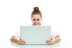 Giovane donna che si siede con un computer portatile Immagini Stock Libere da Diritti