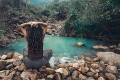 Giovane donna che si siede dal lago in giungle Immagini Stock