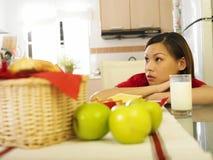Giovane donna che si siede dal suo latte immagine stock libera da diritti