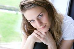Giovane donna che si siede dalla finestra fotografia stock