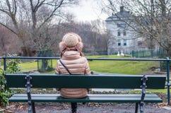 Giovane donna che si siede e che pensa sul banco in parco Fotografie Stock Libere da Diritti
