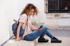 Giovane donna che si siede fuori con il telefono cellulare e le cuffie Immagini Stock Libere da Diritti