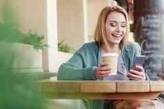 Giovane donna che si siede fuori del caffè con la bevanda calda immagine stock libera da diritti