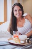 Giovane donna che si siede a letto con una tazza di latte immagini stock
