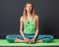 Giovane donna che si siede nel asana di yoga Immagine Stock