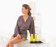 Giovane donna che si siede nel bagno con i cosmetici del bagno Immagine Stock