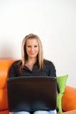 Giovane donna che si siede nel paese per mezzo di un computer portatile Fotografie Stock Libere da Diritti