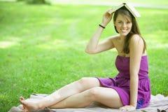 Giovane donna che si siede nel parco con il libro sulla sua testa Immagine Stock