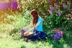 Giovane donna che si siede nel parco sull'erba con i fiori Fotografia Stock