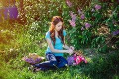 Giovane donna che si siede nel parco sull'erba con i fiori Immagini Stock Libere da Diritti