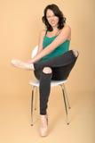 Giovane donna che si siede nell'agonia che regola la sua scarpa Immagine Stock