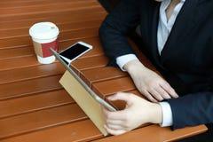 Giovane donna che si siede nella caffetteria alla tavola di legno, caffè bevente e per mezzo del cuscinetto Sulla tavola è il com Immagini Stock