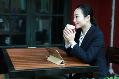 Giovane donna che si siede nella caffetteria alla tavola di legno, caffè bevente e per mezzo del cuscinetto Sulla tavola è il com Fotografie Stock