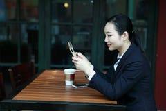 Giovane donna che si siede nella caffetteria alla tavola di legno, caffè bevente e per mezzo del cuscinetto Sulla tavola è il com Immagini Stock Libere da Diritti