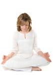 Giovane donna che si siede nella posa meditativa su un fondo bianco Immagine Stock