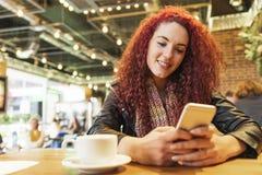 Giovane donna che si siede nella scrittura d'avanguardia del caffè con il suo telefono cellulare Immagini Stock Libere da Diritti