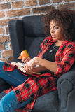 Giovane donna che si siede nella sedia e che studia con i libri mentre mangiando mela Immagini Stock Libere da Diritti