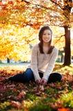 Giovane donna che si siede nelle foglie Immagini Stock