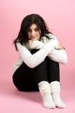 Giovane donna che si siede sopra il colore rosa Fotografia Stock
