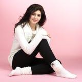 Giovane donna che si siede sopra il colore rosa Fotografie Stock Libere da Diritti