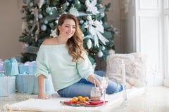 Giovane donna che si siede in stanza con un albero di Natale e contenitori di regalo nei precedenti Donne bionde che sorridono e  immagini stock