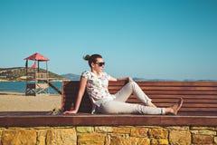 Giovane donna che si siede su un'abbronzatura del sole e del banco Immagini Stock Libere da Diritti