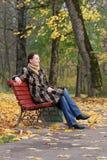 Giovane donna che si siede su un banco Immagini Stock