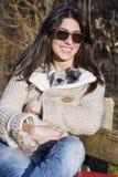 Giovane donna che si siede su un banco che abbraccia il suo cane fotografia stock libera da diritti