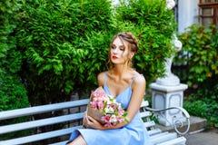 Giovane donna che si siede su un banco con un mazzo dei fiori Fotografie Stock Libere da Diritti