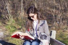 Giovane donna che si siede su un banco nel parco di autunno con il suo cane Fotografia Stock Libera da Diritti