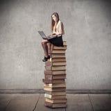Giovane donna che si siede su un mucchio dei libri Fotografie Stock Libere da Diritti
