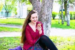 Giovane donna che si siede su un prato inglese verde e che tiene un telefono cellulare Fotografie Stock