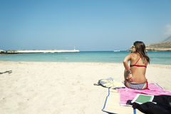 Giovane donna che si siede su una bella spiaggia Immagini Stock