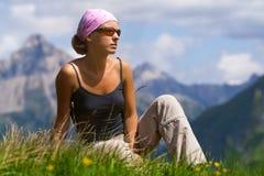 Giovane donna che si siede su una collina Fotografia Stock