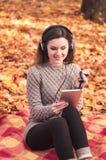 Giovane donna che si siede su una coperta e che ascolta la musica Fotografia Stock