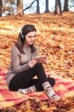 Giovane donna che si siede su una coperta e che ascolta la musica Fotografia Stock Libera da Diritti