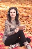 Giovane donna che si siede su una coperta e che ascolta la musica Fotografie Stock Libere da Diritti