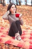 Giovane donna che si siede su una coperta e che tiene una grande tazza rossa Fotografia Stock