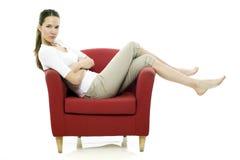 Giovane donna che si siede su una presidenza rossa Immagine Stock